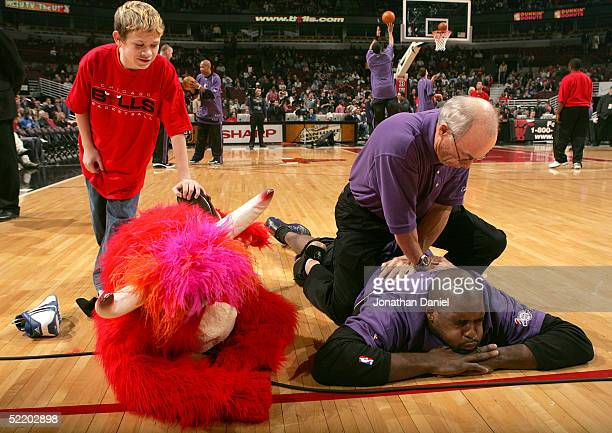 Fan helps the Chicago Bulls Mascot Benny stretch next to Chris Webber of the Sacramento Kings before a game on February 15 2005 at the United Center...