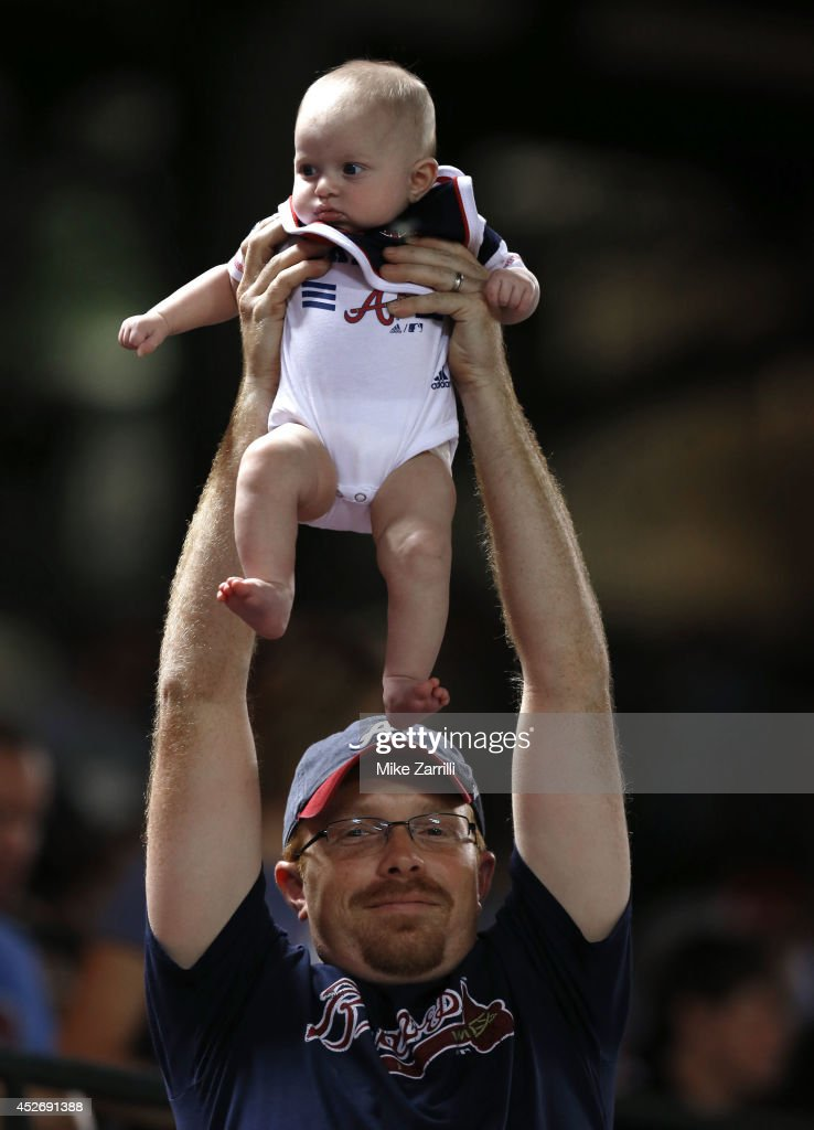 A fan holds a baby under during 'Simba Cam' in between innings of the game between the Atlanta Braves and the San Diego Padres at Turner Field on July 25, 2014 in Atlanta, Georgia.