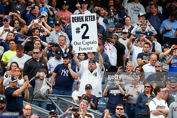 Fan holds a banner in reference to Derek Jeter of the New York Yankees during the eighth inning against the Baltimore Orioles at Yankee Stadium on...