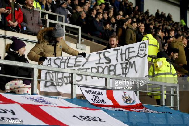 A fan holds a banner protesting against Newcastle United owner Mike Ashley during the FA Cup Fourth Round Replay match between Oxford United and...