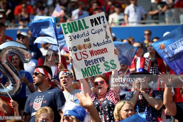 Fan holds a banner protesting the gender pay gap during the 2019 FIFA Women's World Cup France Final match between The United States of America and...