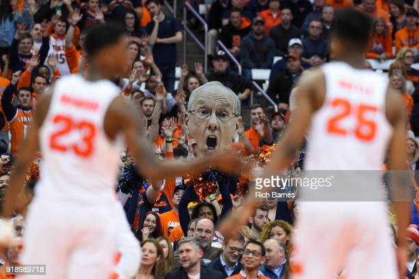 A fan holds a cutout poster of head coach Jim Boeheim of the Syracuse Orange between Frank Howard and Tyus Battle of the Syracuse Orange against the...