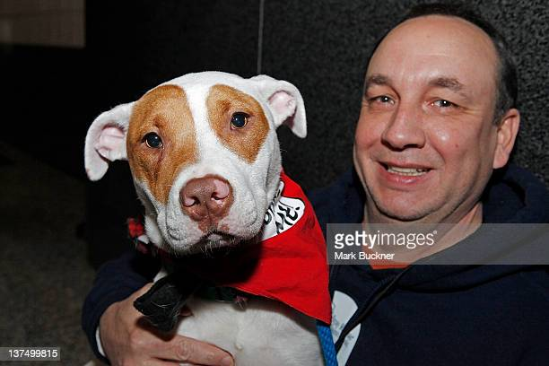A fan holds a dog available for adoption during Barkin' for the Blues a pet adoption event spearheaded by Kelly Backes wife of David Backes of the St...