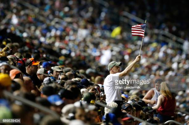 A fan holds a flag during the Monster Energy NASCAR Cup Series CocaCola 600 at Charlotte Motor Speedway on May 28 2017 in Charlotte North Carolina