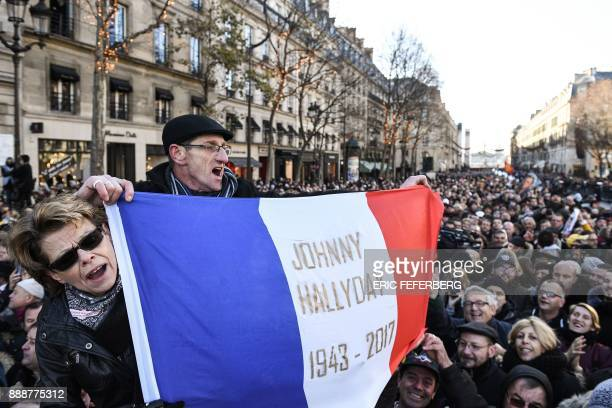 A fan holds a French flag reading 'Johnny Hallyday 19422017' as people gather outside the La Madeleine Church prior to the funeral ceremony in...