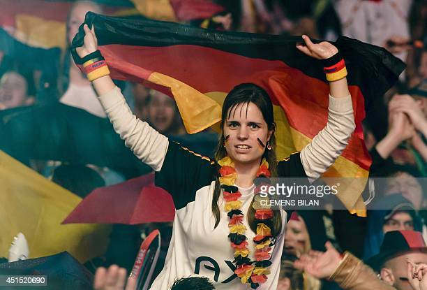 A fan holds a German flag as she watches the the FIFA World Cup 2014 Round of 16 football match between Germany and Algeria on a giant screen in...