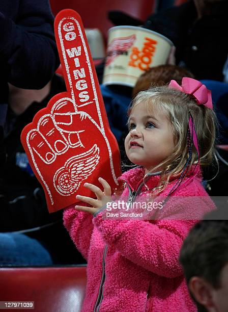 A fan holds a giant foam finger as she watches play between the Pittsburgh Penguins and the Detroit Red Wings during their preseason NHL game at Joe...