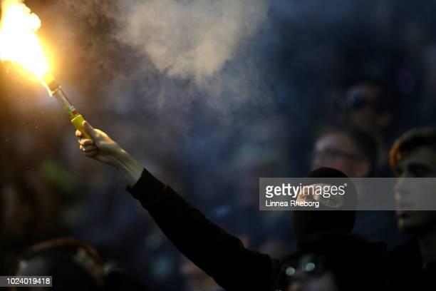A fan holds a lit flare during the Allsvenskan match between AIK and Trelleborgs FF at Friends Arena on August 26 2018 in Stockholm Sweden