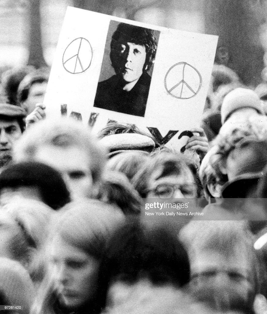 Fan holds a photo of John Lennon as crowd gathers to mourn h : Foto jornalística