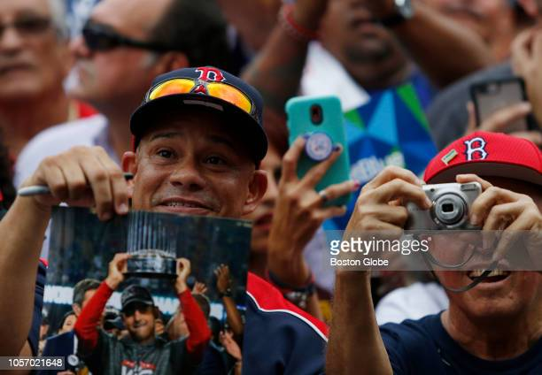 A fan holds a picture of Red Sox manager Alex Cora as he takes the stage with the World Series trophy Red Sox manager Alex Cora and some players took...