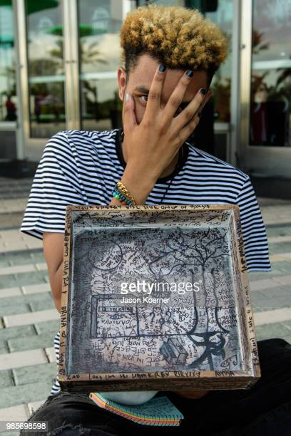 A fan holds a piece of art signed by attendees at a makshift memorial outside the XXXTentacion Funeral Fan Memorial at BBT Center on June 27 2018 in...