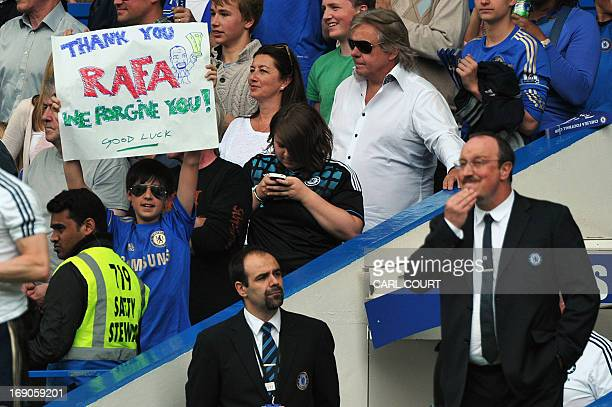 A fan holds a poster that reads 'Thank you Rafa we forgive you' next to Chelsea's Spanish interim manager Rafael Benitez during the English Premier...