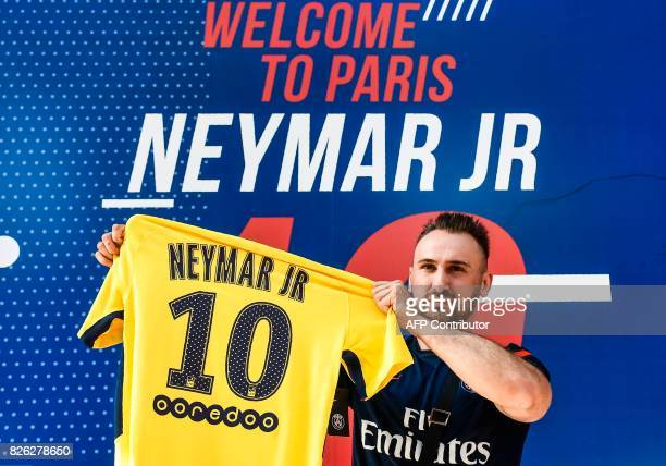 PSG fan holds a PSG yellow away jersey marked with the number 10 and the name of Brazilian star Neymar after he purchased it from the...