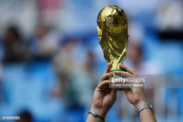 A fan holds a replica of the World Cup trophy during the Russia 2018 World Cup Group B football match between Morocco and Iran at the Saint...