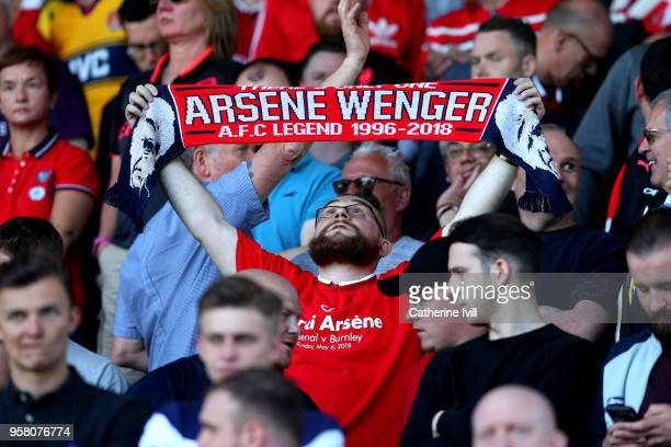 A fan holds a scarf as a tribute to Arsene Wenger Manager of Arsenal during the Premier League match between Huddersfield Town and Arsenal at John...