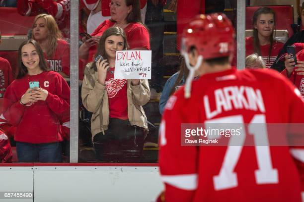 A fan holds a sign as Dylan Larkin of the Detroit Red Wings skates by during warmups prior to an NHL game against the Tampa Bay Lightning at Joe...