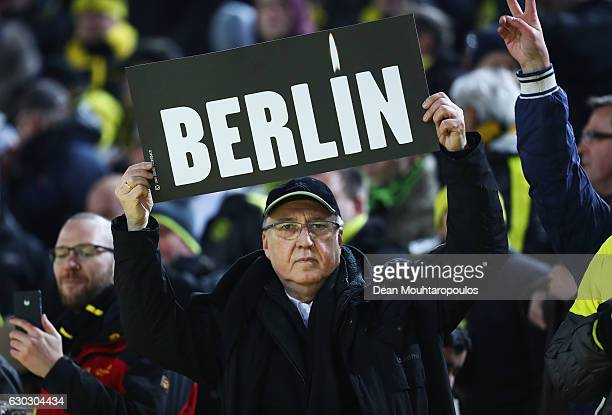 A fan holds a sign as he remembers the victims of the Berlin attack prior to the Bundesliga match between Borussia Dortmund and FC Augsburg at Signal...