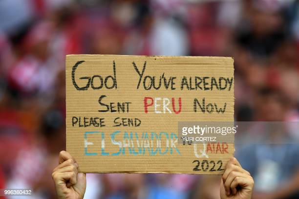 TOPSHOT A fan holds a sign asking God to help El Salvador get qualified for the Qatar 2022 World Cup before the Russia 2018 World Cup semifinal...