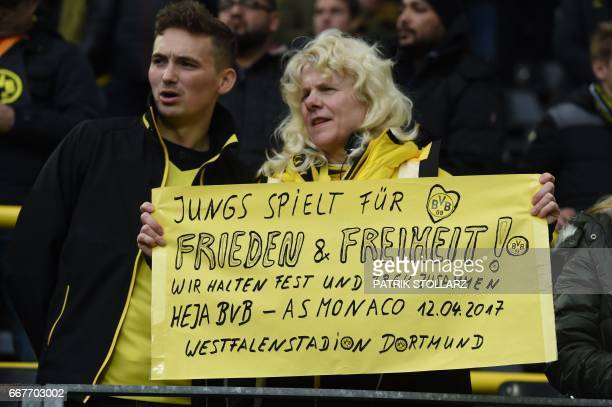 A fan holds a sign reading 'Guys play for peace and freedom' ahead the UEFA Champions League 1st leg quarterfinal football match BVB Borussia...