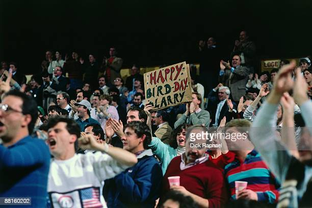 A fan holds a sign that reads 'Happy Bird Day' for Larry Bird of the Boston Celtics during a game played against the Portland Trail Blazers on...