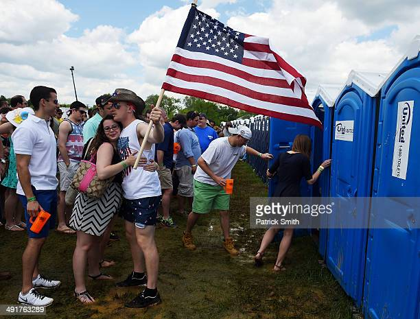 Fan holds an American flag as others wait to use portable toilets in the infield prior to the 139th running of the Preakness Stakes at Pimlico Race...
