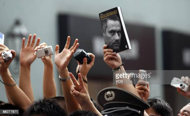 A fan holds an autobiography book of Jose Mourinho coach of FC Inter Milan during Jose Mourinho's visit to Beijing on June 7 2009 in Beijing China