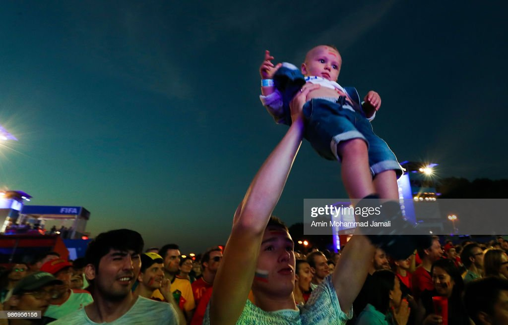 A fan holds up a baby in fan fest of Moscow on June 28, 2018 in Moscow, Russia.