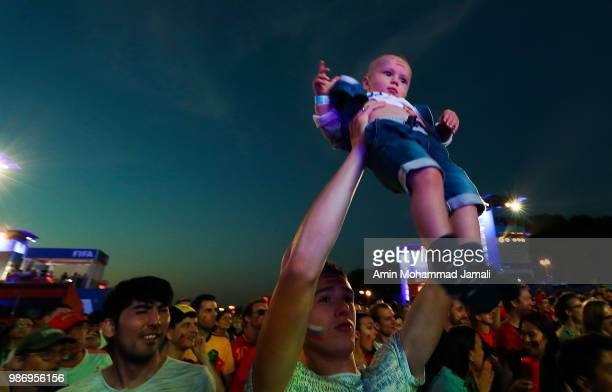 A fan holds up a baby in fan fest of Moscow on June 28 2018 in Moscow Russia