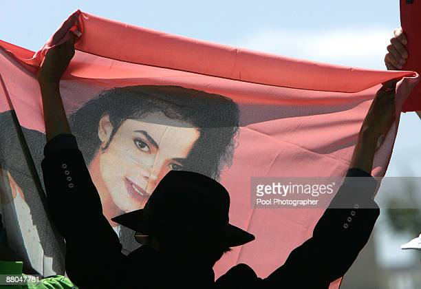 A fan holds up a banner of US pop star Michael Jackson in front of the gates of the Santa Barbara County Courthouse in Santa Maria CA on Thursday...