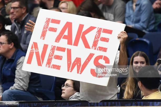 A fan holds up a fake news sign during a college basketball game between the St Bonaventure Bonnies and the George Washington Colonials at the Smith...