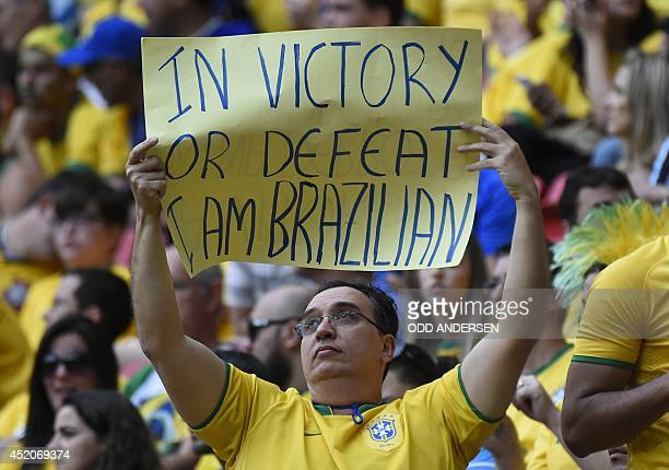 A fan holds up a placard prior to the third place playoff football match between Brazil and Netherlands during the 2014 FIFA World Cup at the...
