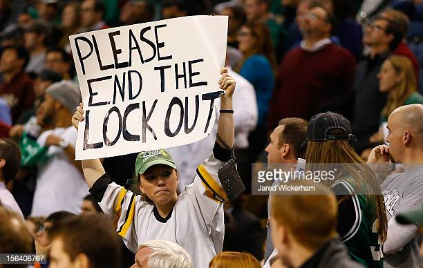 A fan holds up a 'Please end the lockout' sign while wearing a Boston Bruins jersey during the game between the Boston Celtics and the Utah Jazz on...