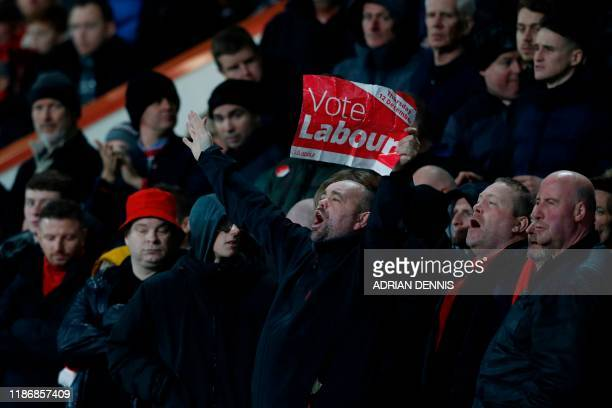 A fan holds up a political Vote Labour poster in the stands during the English Premier League football match between Bournemouth and Liverpool at the...