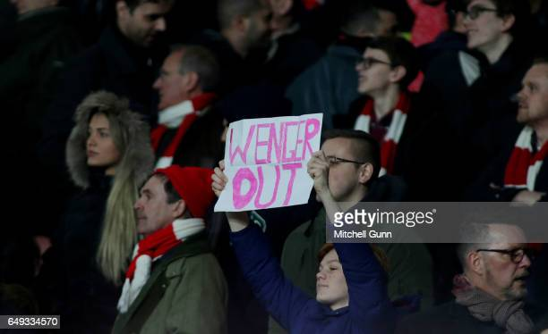 A fan holds up a protest sign saying 'Wenger Out' during the UEFA Champions League Round of 16 second leg match between Arsenal FC and FC Bayern...