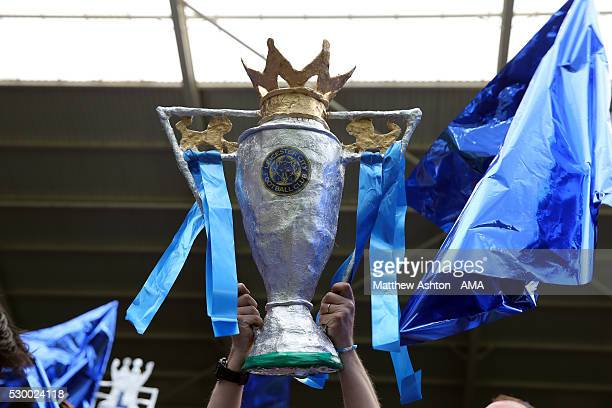 A fan holds up a replica of the Barlcays Premier League trophy during the Barclays Premier League match between Leicester City and Everton at The...