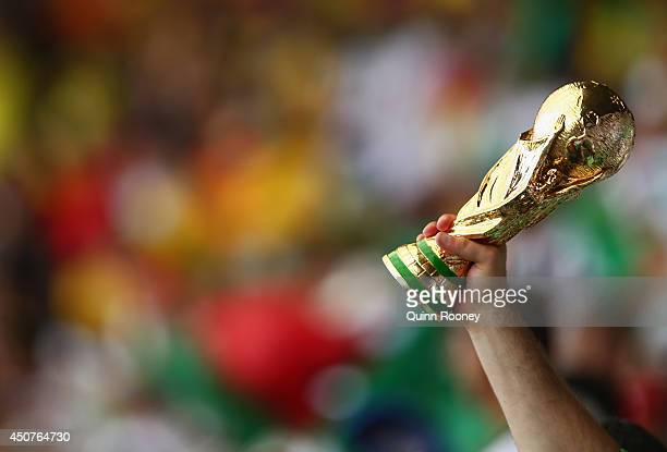 A fan holds up a replica of the World Cup trophy during the 2014 FIFA World Cup Brazil Group H match between Belgium and Algeria at Estadio Mineirao...