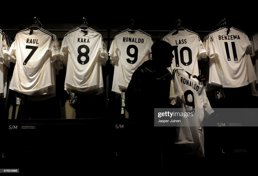 A fan holds up a shirt of Real Madrid player Ronaldo backdropped by shirts of other Real Madrid star players on the day after Real Madrid's UEFA Champions League aggregate defeat against Lyon at the Estadio Santiago Bernabeu on March 11, 2010 in Madrid, Spain.