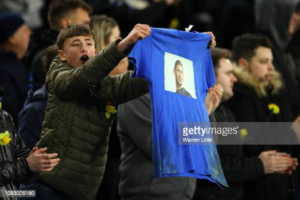 A fan holds up a shirt with showing their respects towards Emiliano Sala during the Premier League match between Cardiff City and AFC Bournemouth at...