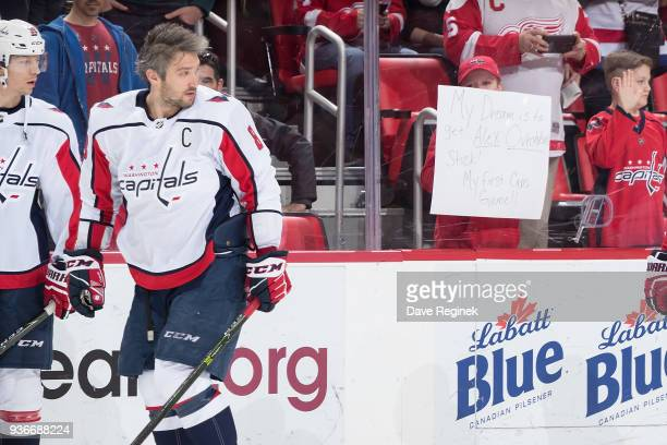 A fan holds up a sign as Alex Ovechkin and Alex Chiasson of the Washington Capitals skate during warmups prior to an NHL game at Little Caesars Arena...