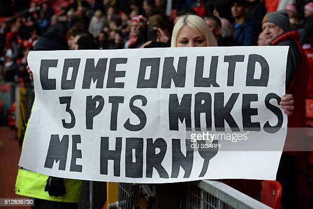 A fan holds up a sign cheering on Manchester United during the English Premier League football match between Manchester United and Arsenal at Old...