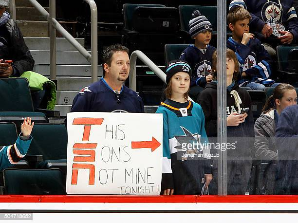 A fan holds up a sign during the pregame warm up showing divided family loyalty prior to NHL action between the Winnipeg Jets and the San Jose Sharks...