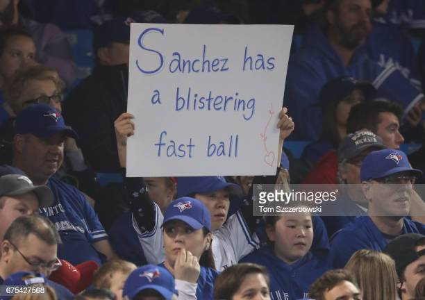 A fan holds up a sign referencing the blister on the pitching hand of Aaron Sanchez of the Toronto Blue Jays during MLB game action against the Tampa...