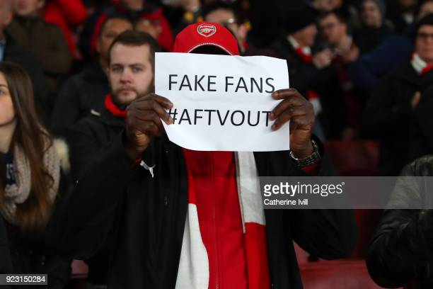 A fan holds up a sign saying Fake fans during UEFA Europa League Round of 32 match between Arsenal and Ostersunds FK at the Emirates Stadium on...