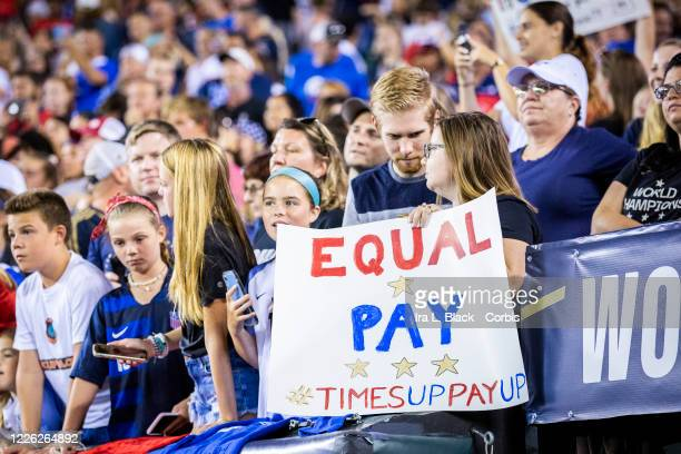 """Fan holds up a sign that says """"Equal Pay Times Up Pay Up"""" in support of the United States Women's National Team fight for equal pay. This was during..."""