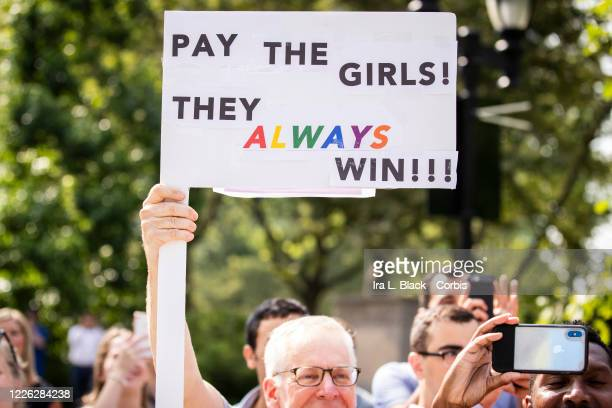 """Fan holds up a sign that says """"Pay the Girls They Always Win!! in support of the United States Women's National Team fight for equal pay. The Ticker..."""