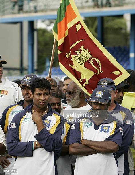 A fan holds up a Sri Lanka flag behing Sri Lankan players Tillakaratne Dilshan and Muttiah Muralitharan after West Indies leveled the series against...