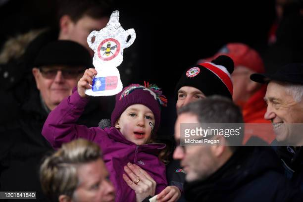 A fan holds up a tin foil replica FA Cup trophy prior to the FA Cup Fourth Round match between Brentford FC and Leicester City at Griffin Park on...