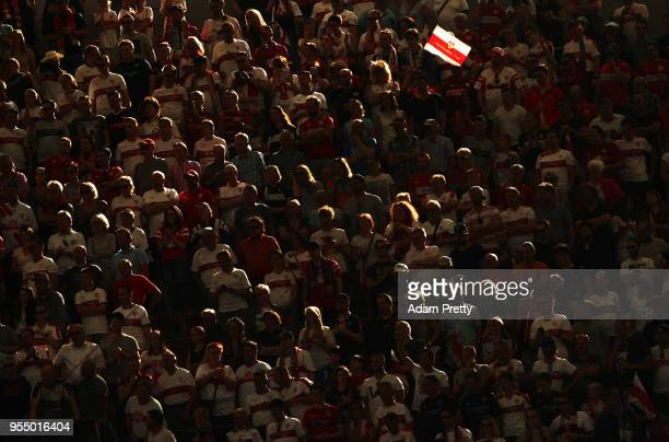 A fan holds up a VfB Stuttgart flag during the Bundesliga match between VfB Stuttgart and TSG 1899 Hoffenheim at MercedesBenz Arena on May 5 2018 in...
