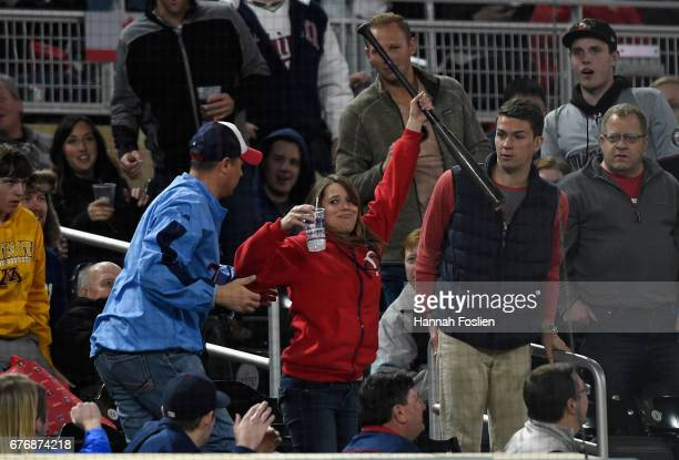 A fan holds up the bat of Byron Buxton of the Minnesota Twins after it flew into the stands during an atbat in the eighth inning of the game against...