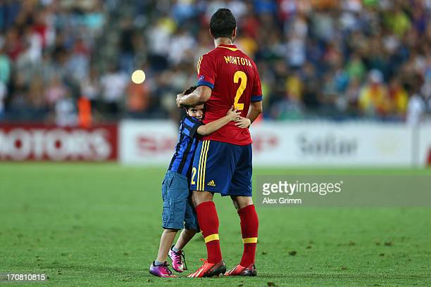 A fan hugs Martin Montoya of Spain after running onto the pitch during the UEFA European U21 Championship final match between Italy and Spain at...